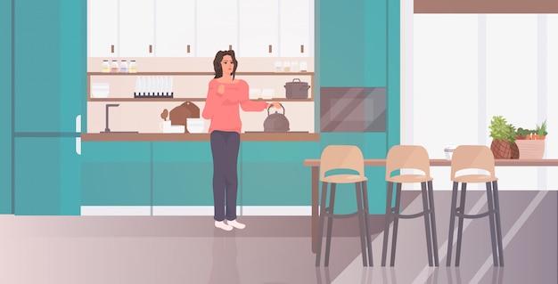 Kobieta trzyma czajnik dziewczyna przygotowuje gorący napój pobyt w domu koronawirusa pandemia kwarantanny koncepcja
