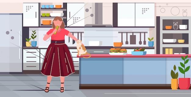 Kobieta trzyma kanapkę z nadwagą dziewczyna jedzenie fast food niezdrowe odżywianie otyłość koncepcja nowoczesna kuchnia wnętrze płaski pełnej długości poziomej