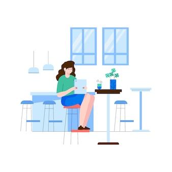 Kobieta trzyma pastylkę w kawiarni