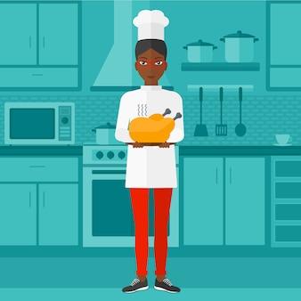 Kobieta trzyma pieczonego kurczaka.