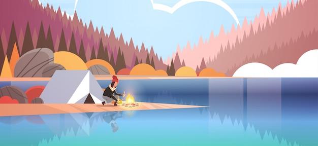 Kobieta turysta płonący ogień w pobliżu namiotu obóz dziewczyna trzyma drewno na ognisko turystyka camping koncepcja jesień krajobraz natura rzeka las góry