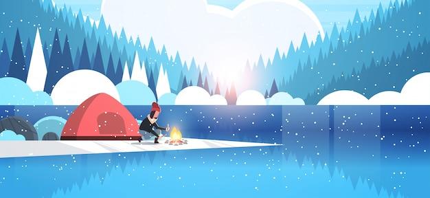Kobieta turysta płonący ogień w pobliżu namiotu obóz dziewczyna trzyma drewno na ognisko turystyka camping koncepcja zimowy krajobraz natura rzeka las góry