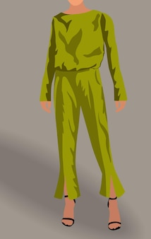 Kobieta ubrana w zieloną bluzkę, spodnie i czarne szpilki.
