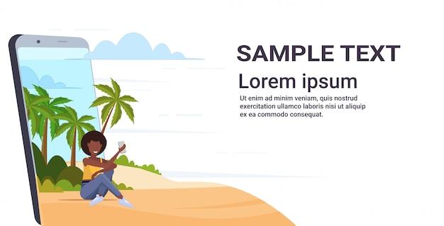 Kobieta używa telefonu komórkowego amerykanina afrykańskiego pochodzenia dziewczyny relaksuje na tropikalnej wyspy morza plaży lata wakacje pojęcia smartphone ekranie online mobilna aplikacja pełnej długości kopii poziomej przestrzeń