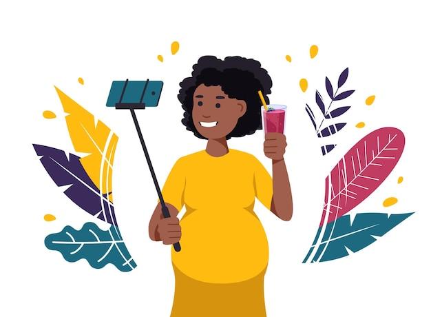 Kobieta w ciąży bierze selfie przy koktajlu.