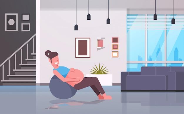 Kobieta w ciąży siedzi na gimnastyczne ćwiczenia z piłką