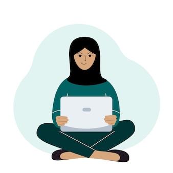 Kobieta w czarnej chuście siedzi i pracuje przy laptopie. muzułmański. praca zdalna lub komunikacja przez internet.