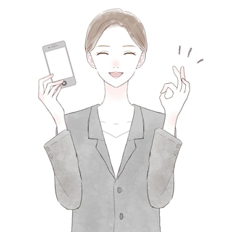 Kobieta w garniturze trzymająca smartfona i trzymająca znak ok. na białym tle.