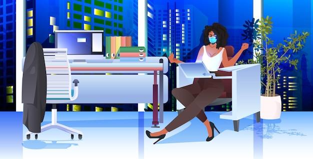 Kobieta w masce siedzi w miejscu pracy i przy użyciu koncepcji pandemii koronawirusa laptopa nowoczesne wnętrza biurowe poziome