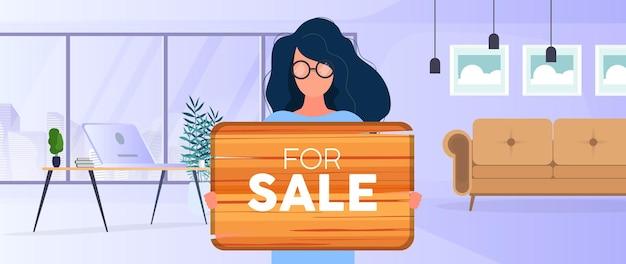Kobieta w okularach trzyma drewniany znak z napisem na sprzedaż. młoda kobieta trzyma drewniany znak. koncepcja sprzedaży mieszkania, biura lub budynku. wektor.