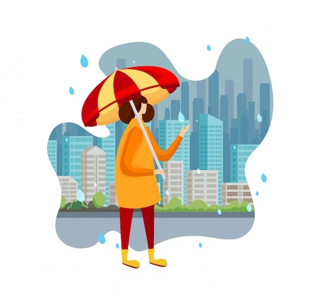 Kobieta w pelerynie i butach trzyma parasol przy deszczem.