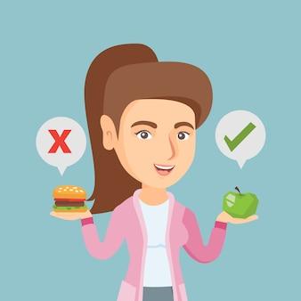 Kobieta wybiera między hamburgerem i babeczką.
