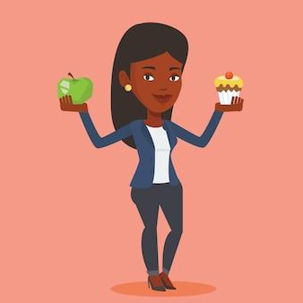 Kobieta wybiera między jabłkiem i babeczką.