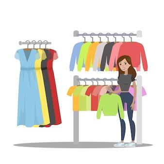 Kobieta wybiera ubrania w sklepie odzieżowym. poszukiwanie modnej bluzy z kapturem. ilustracja