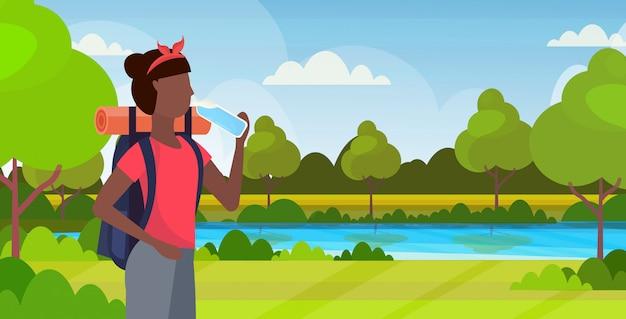 Kobieta wycieczkowicz z plecak wody pitnej afroamerykanin dziewczyna podróżnik na piesze wycieczki koncepcja piękna przyroda krajobraz tło portret płaski poziome