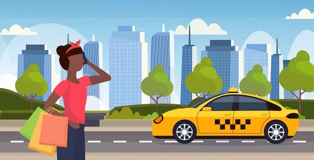 Kobieta z kolorowymi papierowymi torbami zamawia taxi młoda dziewczyna trzyma zakupy duża sprzedaż zakupy pojęcie żeńska postać z kreskówki pejzażu miejskiego tła horyzontalny portret