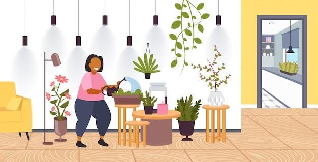Kobieta z konewką dbanie o rośliny doniczkowe dziewczyna dbanie o rośliny domowe pozostać w domu styl życia