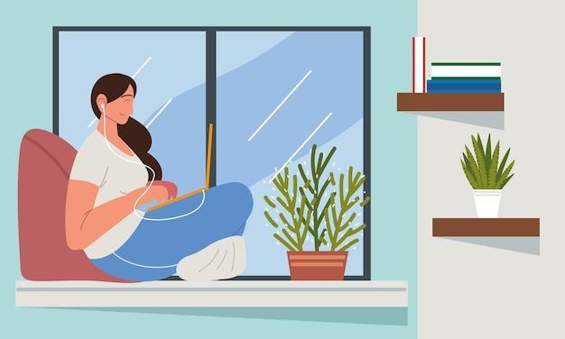 Kobieta z laptopa siedzi okno