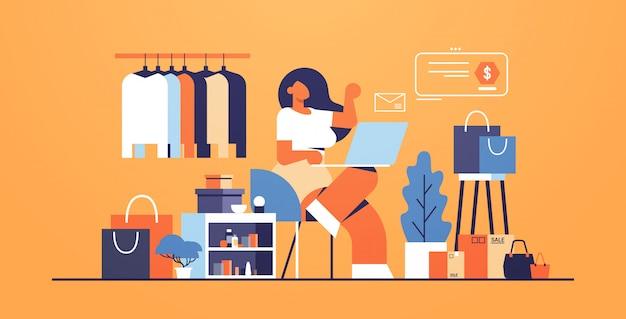 Kobieta z laptopem za pomocą aplikacji komputerowej zakupy online koncepcja duży sklep mody kobiece ubrania butik wnętrze płaskie pełnej długości poziomej