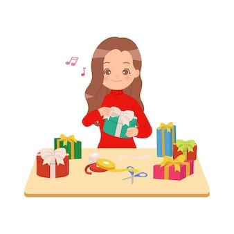 Kobieta zawijająca stos prezentów i ozdabiająca ją wstążkami.