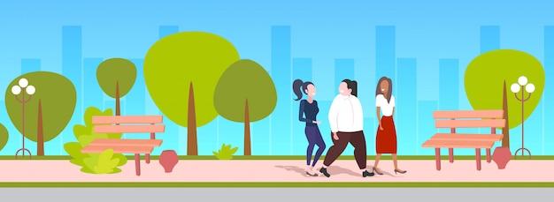Kobiety dyskutujące podczas spaceru na świeżym powietrzu mieszać rasy dziewcząt o dyskusji przyjaźń koncepcja otyłości miejskiego parku pejzaż miejski