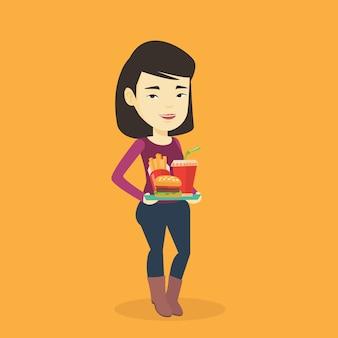 Kobiety mienia taca pełno fast food.