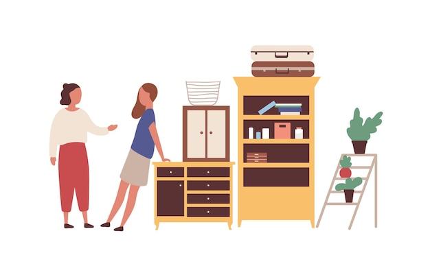 Kobiety na pchlim targu ilustracja wektorowa płaski. kreskówka dziewczyny, sąsiedzi spotykają się na wyprzedaży garażowej. kobieta kupujący pyta o cenę starych mebli. klienci sklepów z odzieżą używaną, którzy kupują antyki.