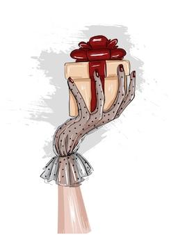 Kobiety ręka w rękawiczce trzyma prezent