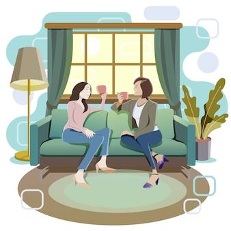Kobiety siedzą na kanapie. picie herbaty i rozmawianie.