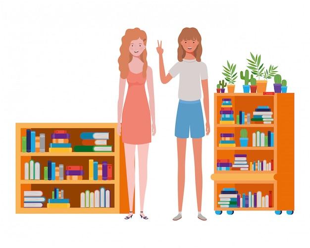 Kobiety stojące z regał z drewna i książek