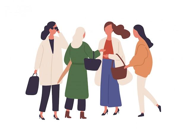 Kobiety w sezonie jesiennym modne stroje płaska ilustracja. stylowa kobieta ze smartfonami i torebkami chodzić razem na białym tle. kobiece postacie stojące w jesienne płaszcze.