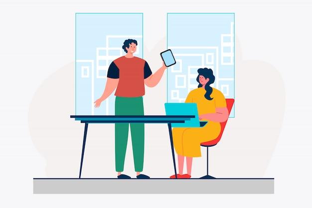 Koledzy z biura korzystający z urządzeń cyfrowych
