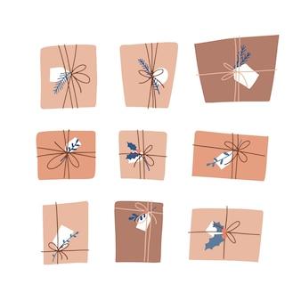 Kolekcja różnych świątecznych prezentów i prezentów z papieru rzemieślniczego z zielonymi gałązkami w skandynaw...