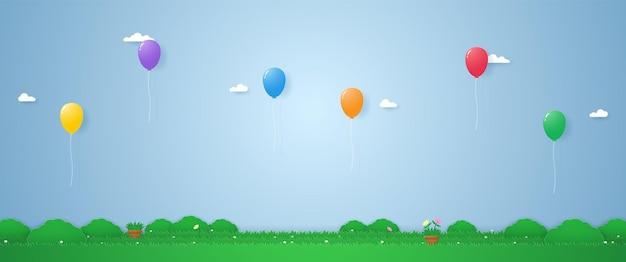Kolorowe balony unoszące się nad trawą w stylu sztuki papieru