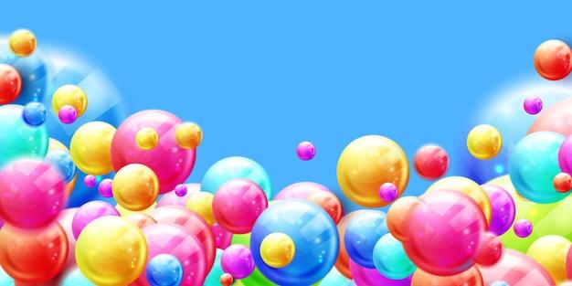 Kolorowe błyszczące kulki cukierków na żółtym tle