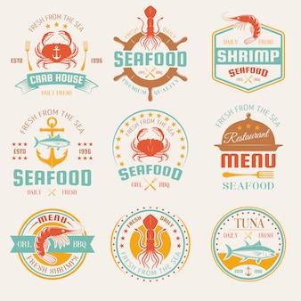 Kolorowe emblematy restauracji z owocami morza ze sztućcami i kloszami, kotwicą i hełmem na białym tle