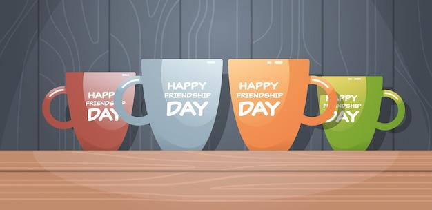 Kolorowe kubki na drewnianym stole z tekstem szczęśliwy dzień przyjaźni uroczystości