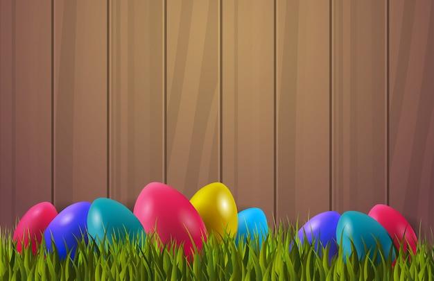 Kolorowi wielkanocni jajka na zielonej trawie nad drewnianym textured tłem z copyspace