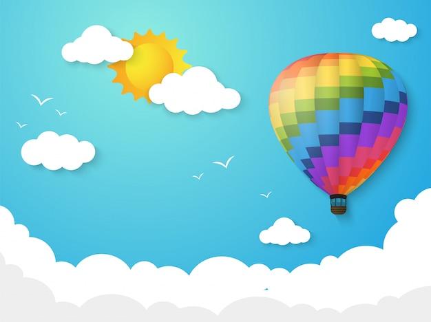 Kolorowy balon pływający po niebie z porannym słońcem.