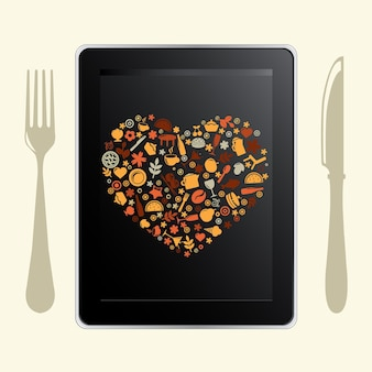 Komputer typu tablet i ikony żywności, na białym tle,
