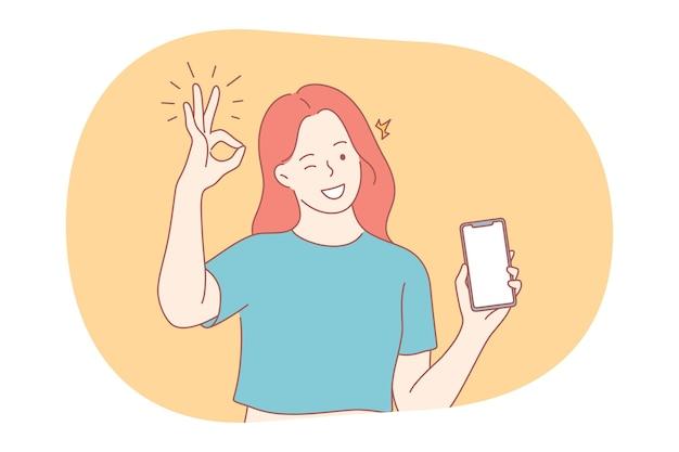 Komunikacja online, kciuki w górę, koncepcja smartfona. młoda uśmiechnięta dziewczyna pokazuje ekran smartfona