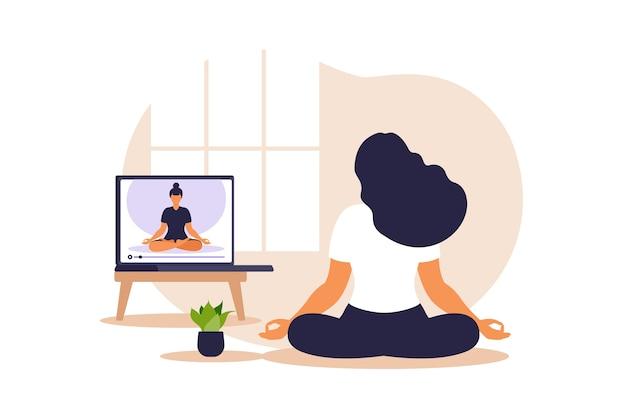Koncepcja jogi online z afrykańską kobietą robi ćwiczenia jogi w domu z instruktorem online.