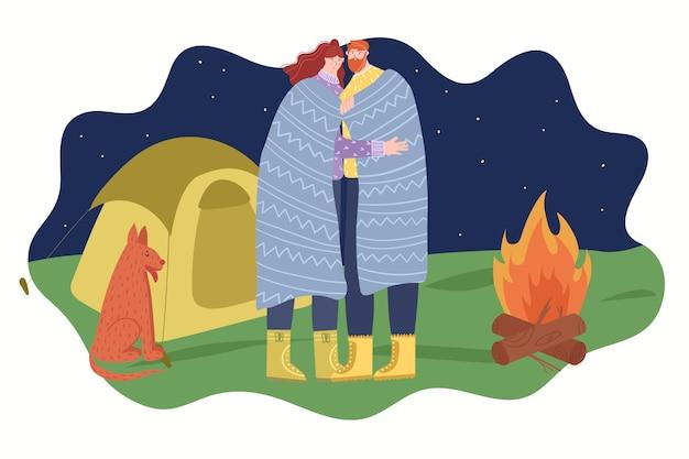 Koncepcja kempingu. zakochana para stoi w objęciach w pobliżu ogniska w nocy.