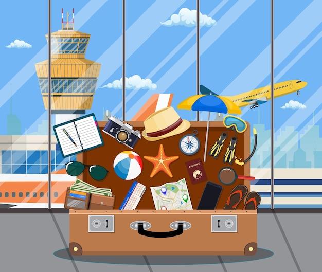 Koncepcja międzynarodowego lotniska. letnie wakacje, turystyka i przedmioty wakacyjne. torba na kompas aparatu fotograficznego, portfel, mapa, maska do nurkowania, klapki, płaski portfel na kapelusz