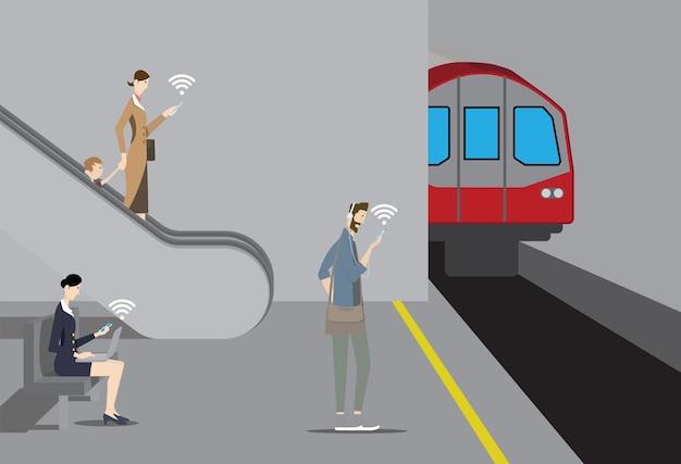 Koncepcja publicznego bezpłatnego wifi. pasażerowie korzystają ze swoich urządzeń mobilnych na peronie metra.