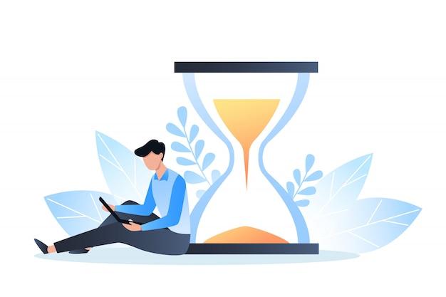 Koncepcja zarządzania czasem, organizacja czasu pracy, termin, młody człowiek siedzi z laptopem w pobliżu klepsydry