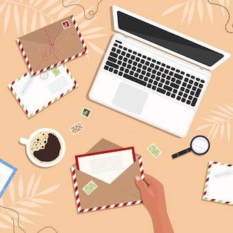 Koperta z listem w rękach na stole. laptop i kartki pocztowe ze znaczkami w miejscu pracy i kobieta otwiera kopertę w stylu płaskiej