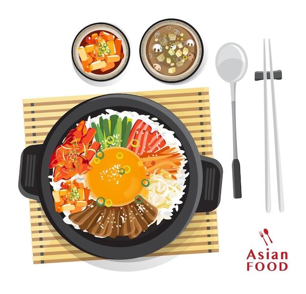 Koreański zestaw bibimbap, mieszanie ryżu z różnymi składnikami w czarnej misce, widok z góry