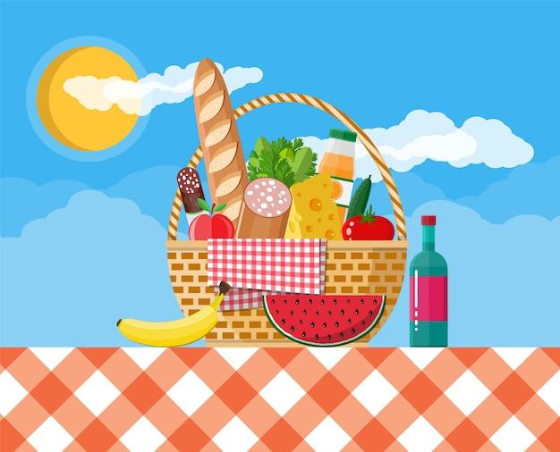 Kosz piknikowy wicker pełen produktów.