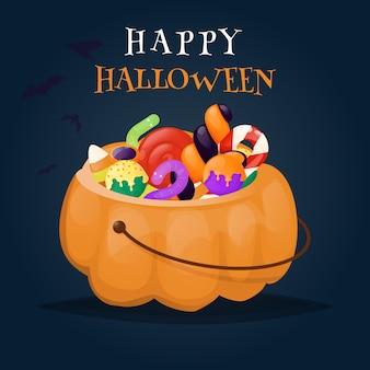 Kosz z dyni halloween pełen cukierków i słodyczy.